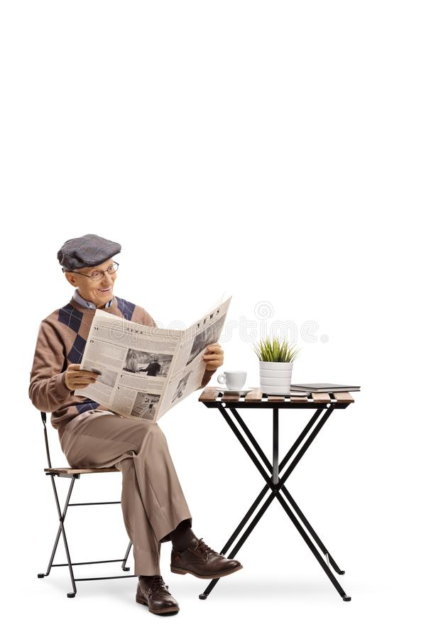 Elderly man sitting at a coffee table and reading a newspaper royalty free stock image