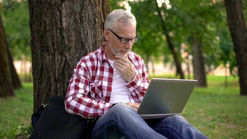 Elderly man sitting on grass and chatting online on laptop, dating applications royalty free stock photography