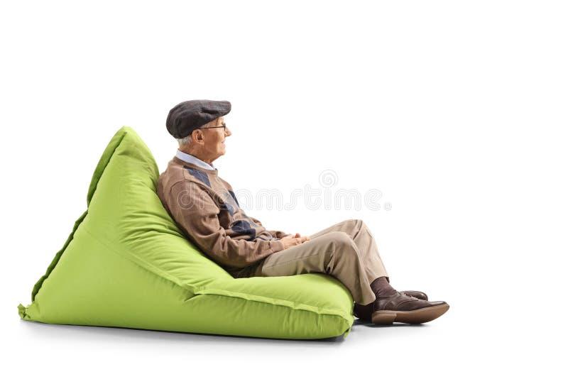Elderly man sitting on a green bean bag. Full length profile shot of an elderly man sitting on a green bean bag isolated on white background stock photography