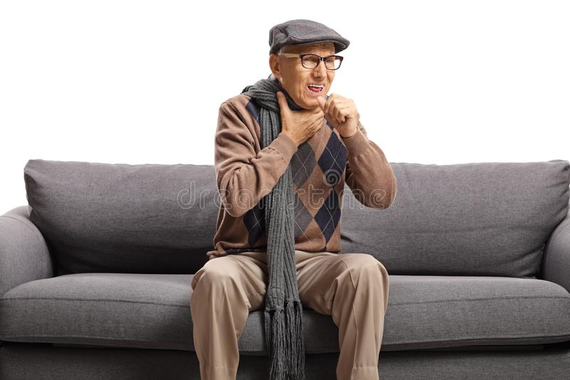 Elderly man sitting on a sofa and cauging stock image