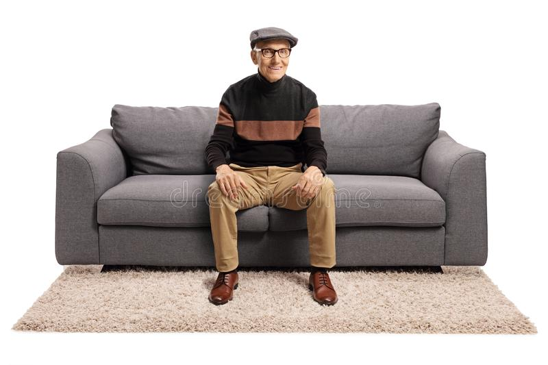 Elderly man sitting on a sofa and smiling stock photo
