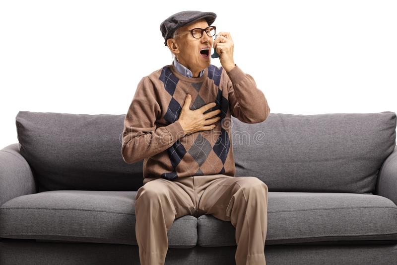 Elderly man sitting on a sofa and using an inhaler royalty free stock photography