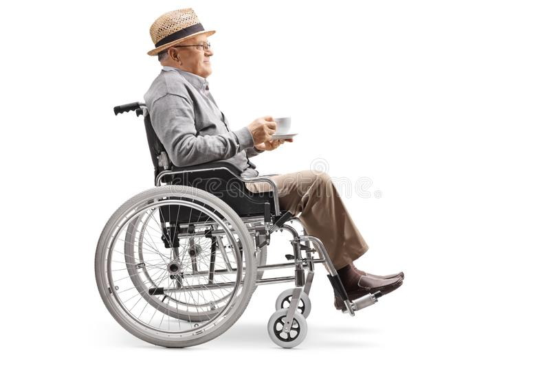 Elderly man sitting in a wheelchair with a cup of coffee. Full length profile shot of an elderly man sitting in a wheelchair with a cup of coffee isolated on royalty free stock photography