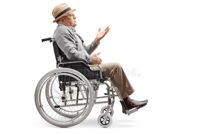 Elderly man sitting in a wheelchair and gesturing a conversation. Full length profile shot of an elderly man sitting in a wheelchair and gesturing a conversation royalty free stock image