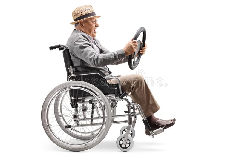 Elderly man sitting in a wheelchair and holding a steering wheel from a car. Full length profile shot of an elderly man sitting in a wheelchair and holding a stock images
