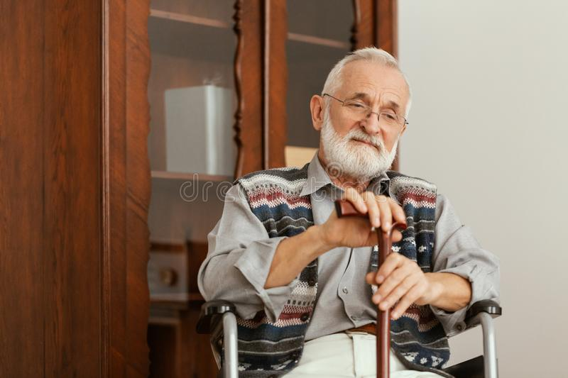 Elderly man sitting on a wheelchair and supporting himself with cane stock photography