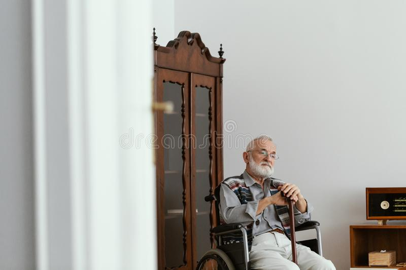 Elderly man sitting on a wheelchair and supporting himself with cane royalty free stock photo