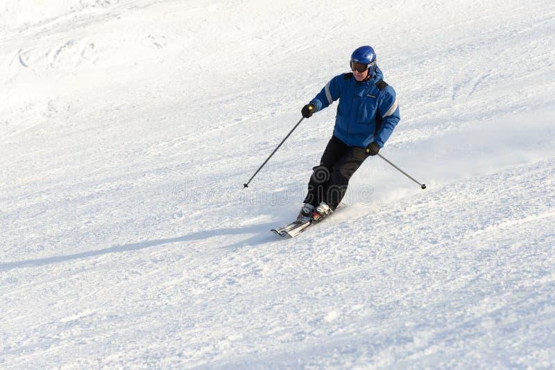 Elderly man skiing down ski slope stock photo