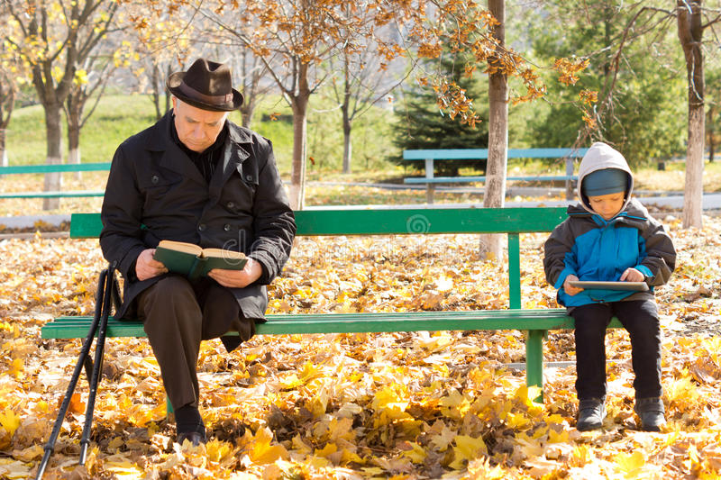 Elderly man and small boy sitting on a park bench royalty free stock photography