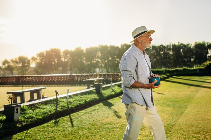 Elderly man standing in a lawn holding a boule royalty free stock image