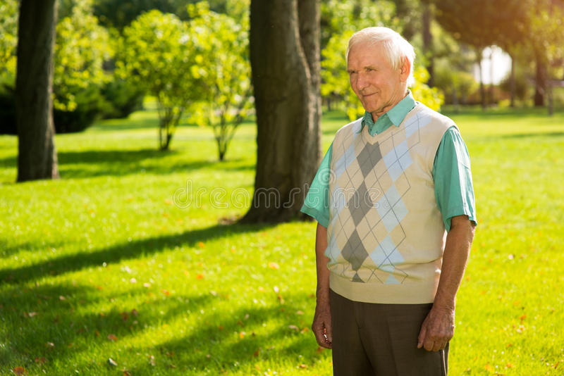 Elderly man standing outdoor. Person slightly smiling. Philosophy of life. Don't regret your choices royalty free stock images