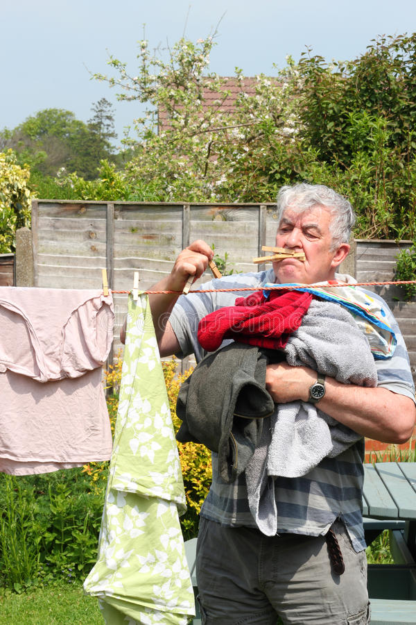 Elderly man stressed hanging out the laundry. royalty free stock photo