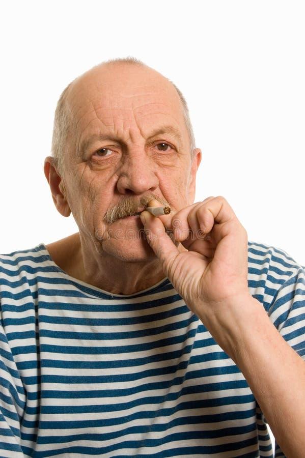 Elderly man in a stripped vest smokes