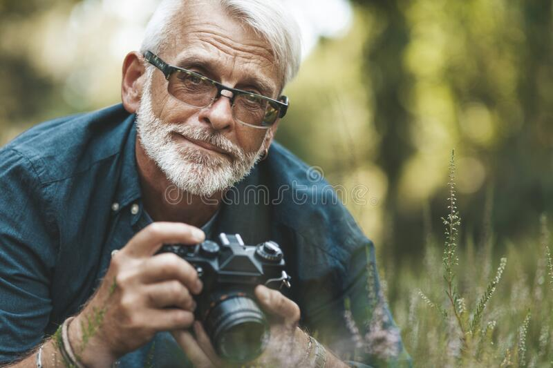 Elderly man takes pictures of flowers in park, pensioner on walk. Active hobby of mature person stock photos