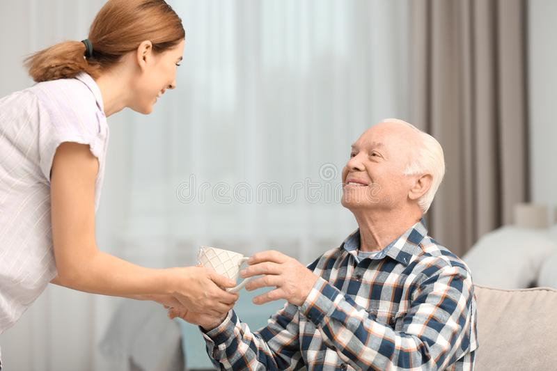 Elderly man taking cup of tea from female caregiver stock photography