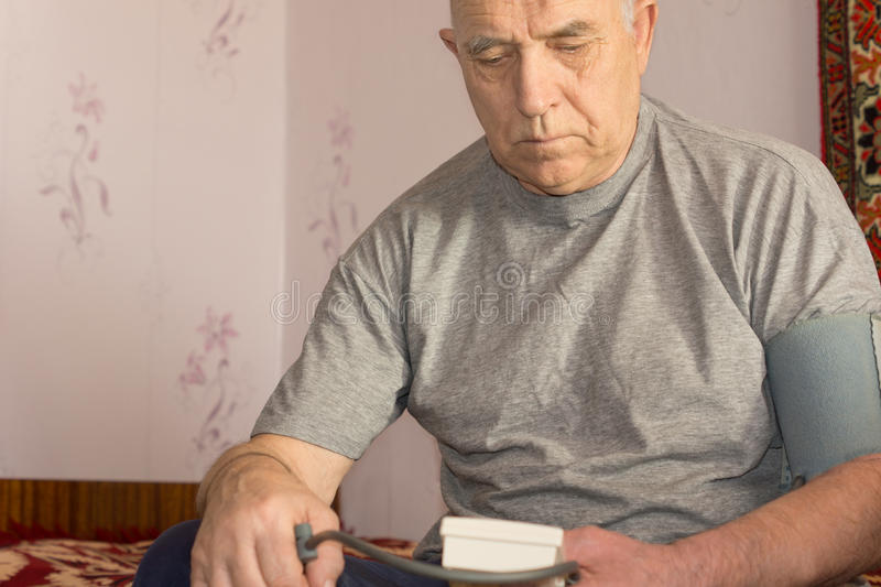 Elderly man taking his blood pressure. Using a pressure cuff and sphygmomanometer to test for hypertension stock photo