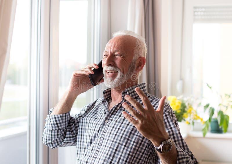 Elderly man talking on phone a home royalty free stock photos