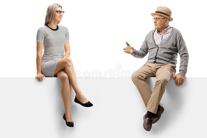 Elderly man talking to a young blond woman while sitting on a panel royalty free stock photography