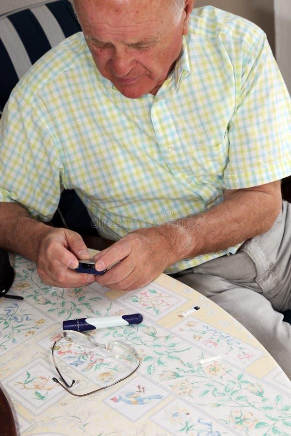 Elderly man testing his glucose level royalty free stock images