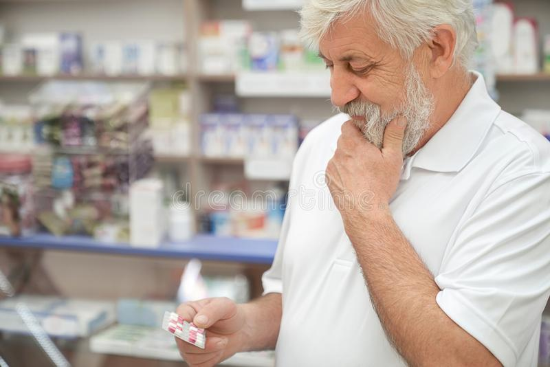 Elderly man thinking, holding pills in pharmacy. royalty free stock image
