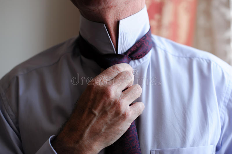 An elderly man ties a tie around his neck. The old man dressed for the meeting. The dress code for men stock photo