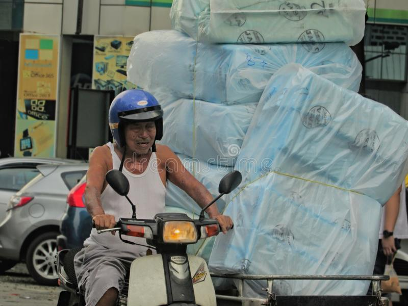 Elderly Man Transporting Polystyrene Lunch Boxes. An elderly man transporting bags of polystyrene take-away lunch boxes on the sidecar of his motorbike in the stock photography