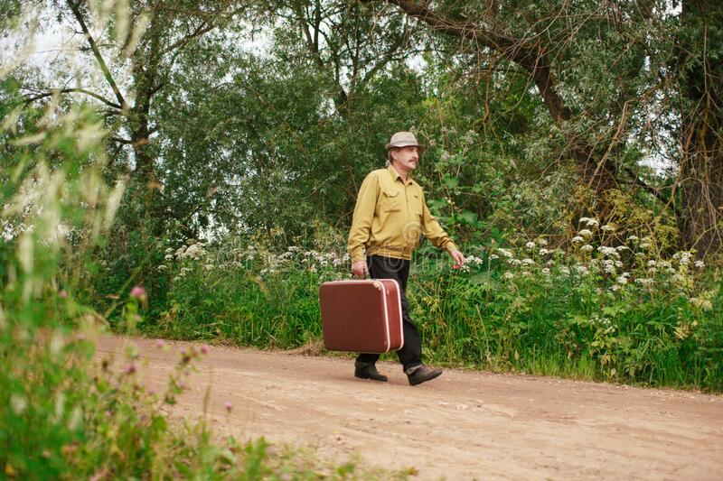 An elderly man travels with a suitcase. A sad and tired villager is on the road to a long way royalty free stock photos