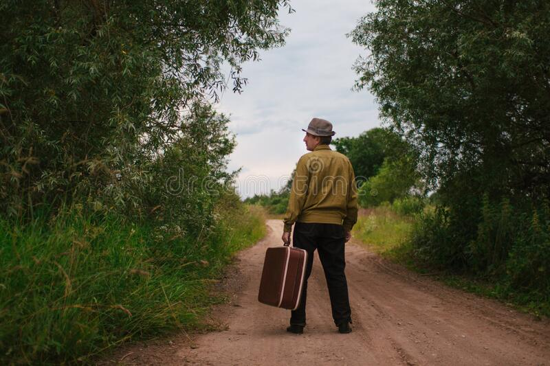 An elderly man travels with a suitcase. A sad and tired villager is on the road to a long way royalty free stock images