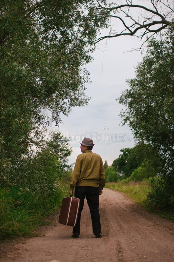An elderly man travels with a suitcase. A sad and tired villager is on the road to a long way stock image