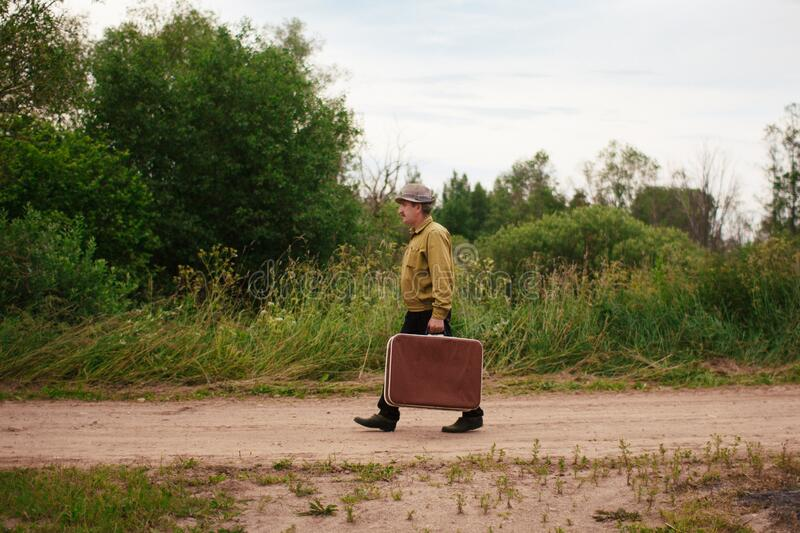 An elderly man travels with a suitcase. A sad and tired villager is on the road to a long way royalty free stock photo