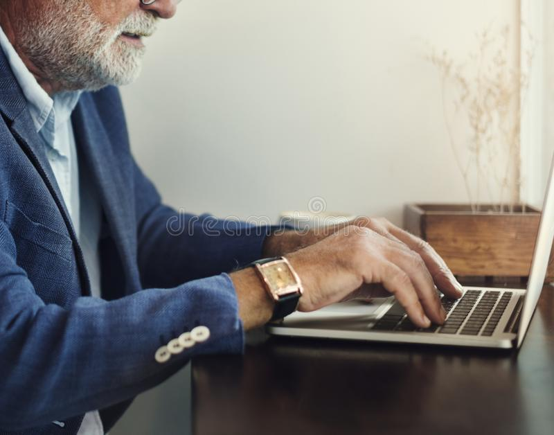 Elderly man is using computer laptop royalty free stock photos