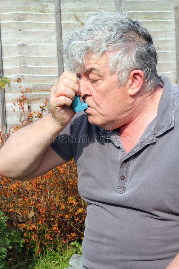 Elderly man using inhaler. royalty free stock photos