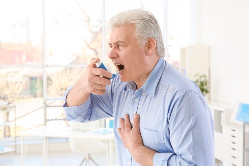 Elderly man using inhaler stock image