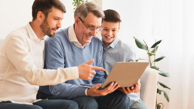 Elderly Man Using Laptop Sitting Between Son And Grandson Indoor royalty free stock photography