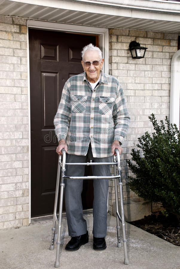 Elderly Man With Walker. A 93 year old handicapped man, with a walker, standing outside in front of his apartment stock photo