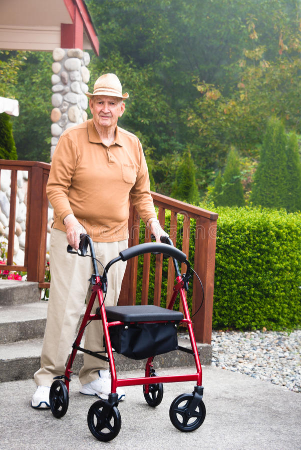 Elderly Man with Walker. Vertical image of an elderly man standing with his walker in front of the front steps of a house. Morning fog helps blurs the green stock images