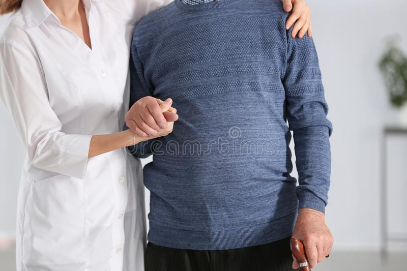Elderly man with walking cane and female caregiver. On blurred background, closeup stock photo