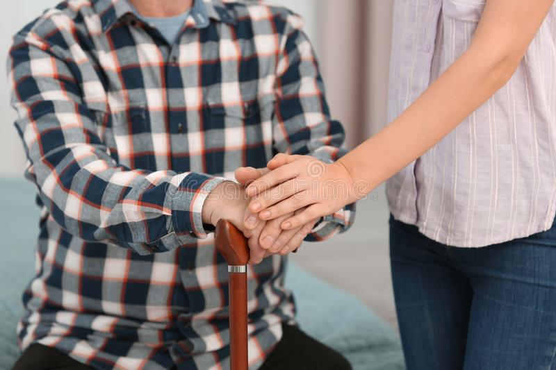 Elderly man with walking cane and female caregiver. On blurred background, closeup view stock image