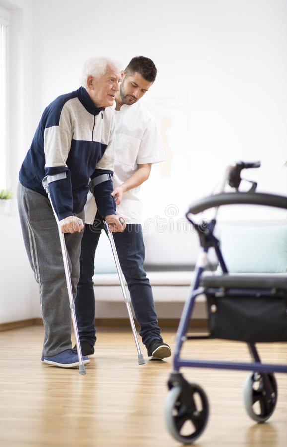 Elderly man walking on crutches and a male nurse supporting him. Elderly men walking on crutches and a helpful male nurse supporting him royalty free stock photos