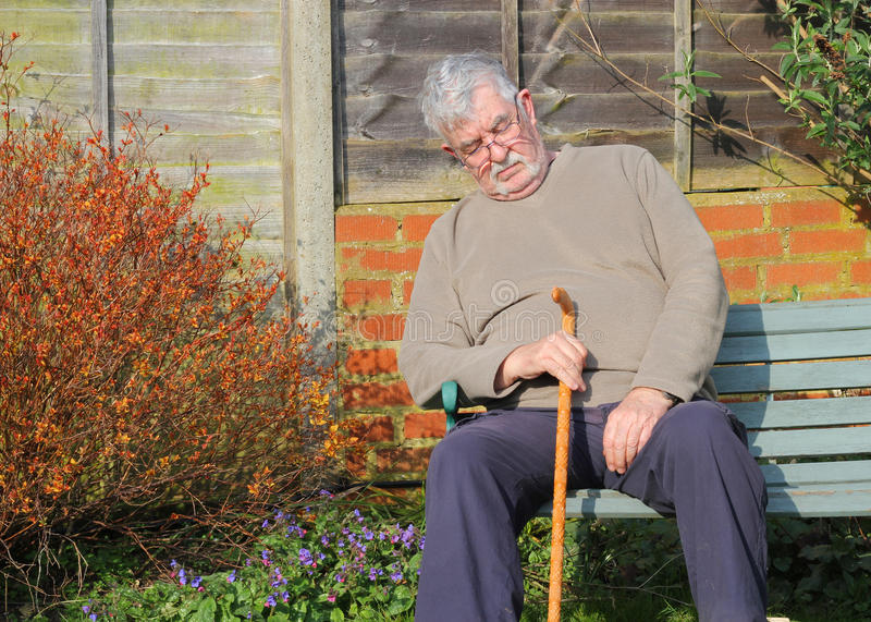 Elderly man with walking stick asleep. stock photos