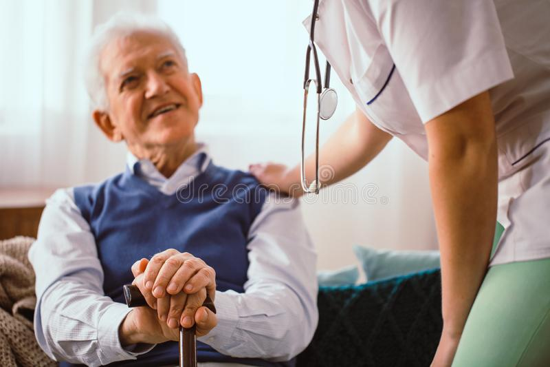 Elderly man with stick being comforted by doctor in nursing home. Elderly man with walking stick being comforted by doctor in nursing home royalty free stock image