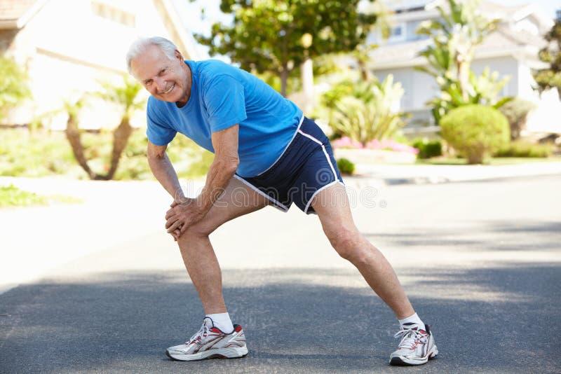 Elderly man warming up for run royalty free stock image