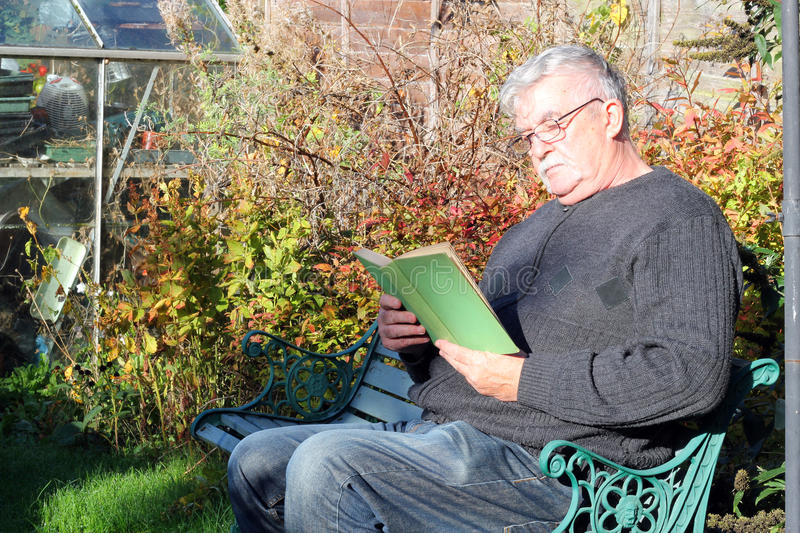 Elderly man wearing eyeglasses and reading a book royalty free stock images