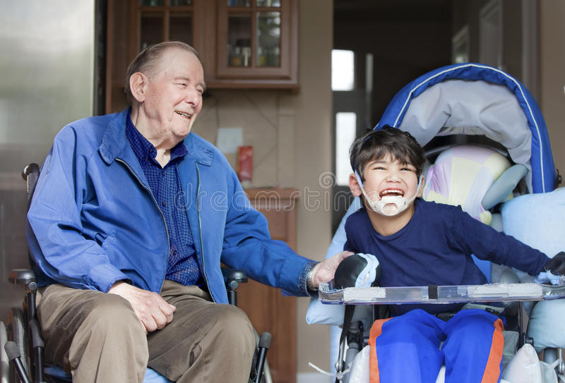 Elderly man in wheelchair with disabled boy. Elderly men in wheelchair laughing with disabled boy in kitchen royalty free stock photography