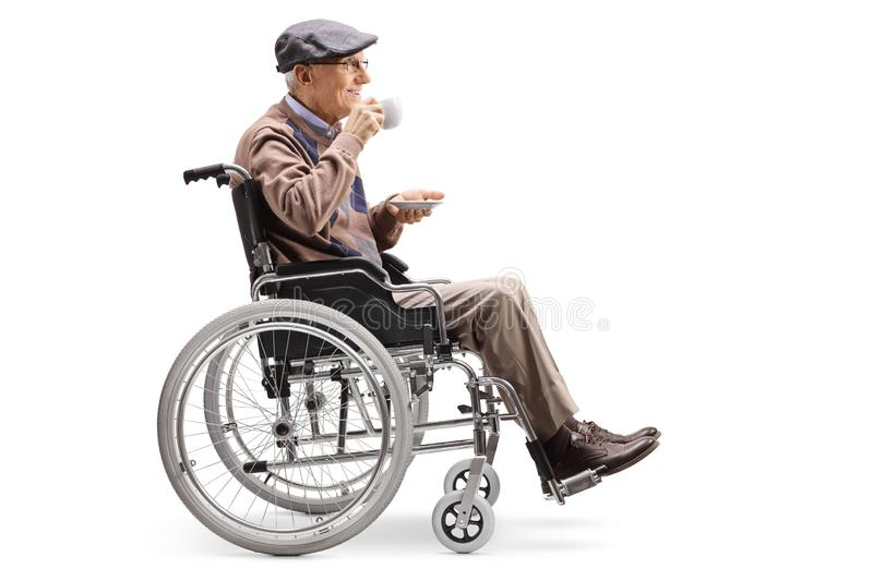 Elderly man in a wheelchair drinking a cup of coffee. Full length profile shot of an elderly man in a wheelchair drinking a cup of coffee isolated on white stock images