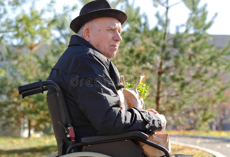 Elderly man in a wheelchair enjoying the sun. Sitting outdoors in a hat and overcoat with a bag of groceries on his lap royalty free stock image