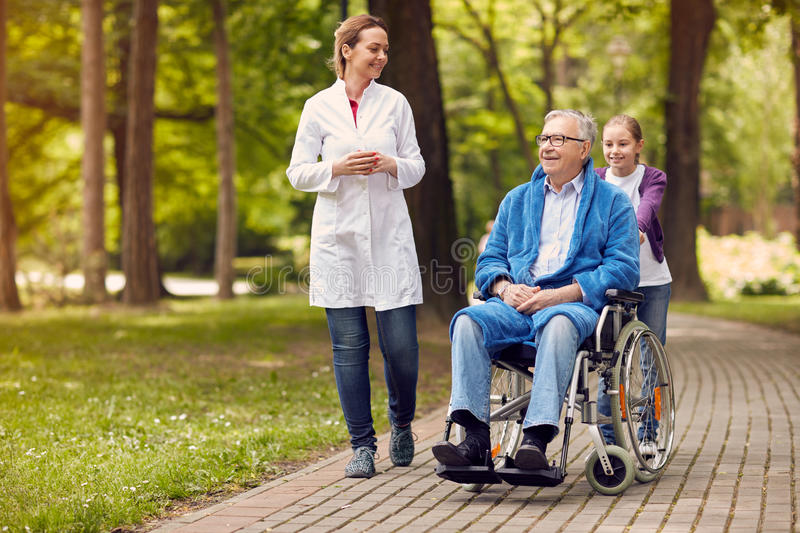 Elderly man on wheelchair with nurse and granddaughter outdoor royalty free stock image