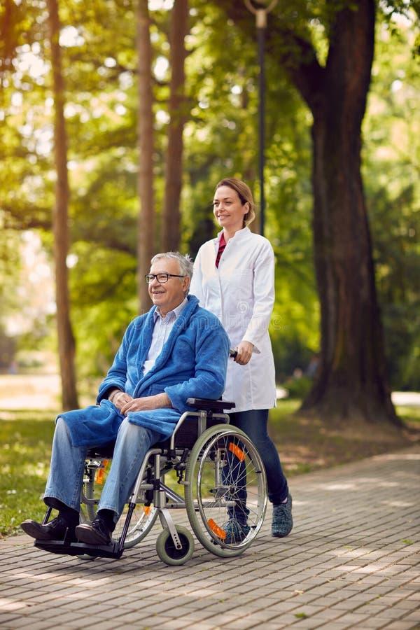 Elderly man on wheelchair with nurse outdoor stock photography