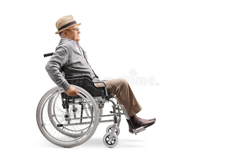 Elderly man in a wheelchair pushing himself manually. Full length profile shot of an elderly man in a wheelchair pushing himself manually isolated on white stock photos