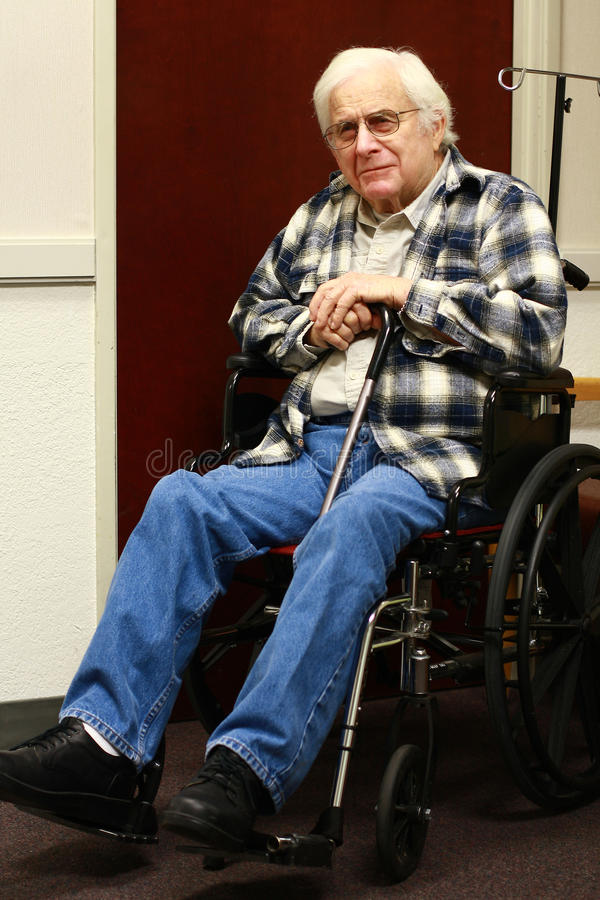 Elderly man in wheelchair smiles stock image